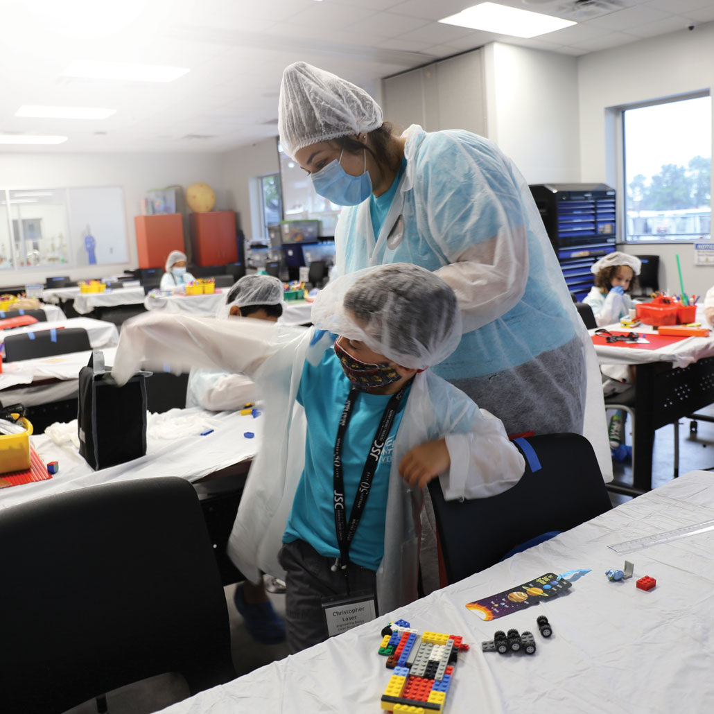 kids wearing protective gear in a cleanroom